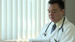 Doctor looking over charts and looking upset Stock Footage