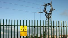 Electrical tower on blue sky with yellow personalized warning signboard Stock Footage