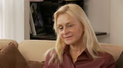 Blonde Woman Sitting on Couch Stock Footage