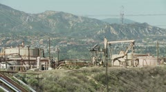 Oil well pumping oil, with tanks. Stock Footage