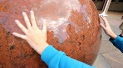 Huge wet marble sphere being spun by hands Stock Footage