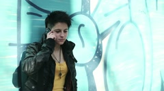 Young punk girl talking on cellphone by the wall, steadicam shot HD Stock Footage