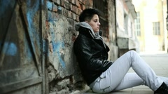 Young sad punk girl sitting by the wall HD - stock footage