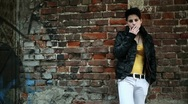 Young punk girl smoking cigarette by the brick wall, steadicam shot HD Stock Footage