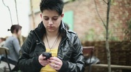 Young punk girl using smartphone in the city, steadicam shot HD Stock Footage