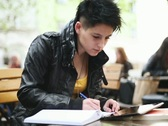 Young student with notebook and digital tablet in bar, steadicam shot NTSC Stock Footage