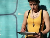 Punk girl with tablet computer standing by the wall, steadicam shot NTSC Stock Footage