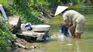 Vietnamese woman washes clothes Vietnam Stock Footage