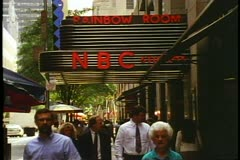 The NBC Marquee at Rockefeller Center in New York City, people pass under Stock Footage