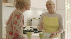 Mother and daughter talking, drinking coffee in kitchen at home Stock Footage