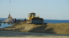 Bulldozer working on the beach. - stock footage