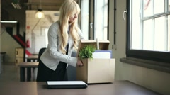 Happy businesswoman unpacking her belongings from box in the office HD Stock Footage