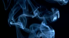 Smoke spirals up through frame Stock Footage