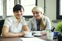 Two happy young businesswomen gossip in the office NTSC Stock Footage