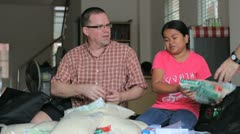 Missionary Packs Up Rice In A Care Package - stock footage
