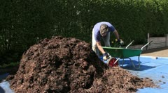 Man putting manure into wheelbarrow Stock Footage