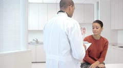 Doctor consulting patient in exam room - stock footage