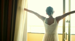 Girl opens the curtains in the morning HD Stock Footage