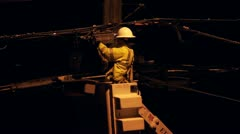 Utility worker on pole at night Stock Footage
