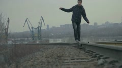 Young man goes to rail against backdrop of the city - stock footage