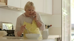 Retired woman speaking on telephone and preparing food at home - stock footage