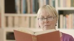 Happy senior woman with glasses reading book at home Stock Footage