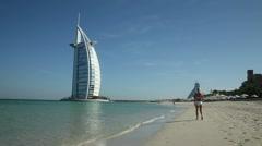 Walking on Jumeirah Beach towards the Burj Al Arab hotel, Dubai Stock Footage