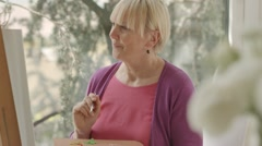 Happy elderly woman painting for fun at home - stock footage