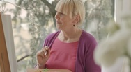 Happy elderly woman painting for fun at home Stock Footage