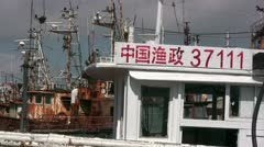 Chinese characters on a new fishing boat in front of old fishing fleet Stock Footage