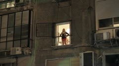 506 young woman watches something from her window Stock Footage