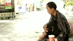 Homeless Asian Man Begging on a Sidewalk Stock Footage