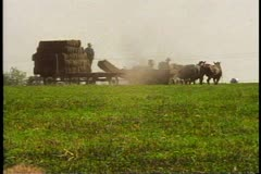 Amish farmers with a hay wagon, hay bales being loaded, near Lancaster Stock Footage