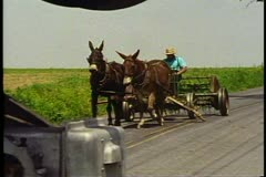 Amish man drives team of horses and a cart over railroad tracks near Lancaster Stock Footage