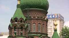 Contrast - Chinese advertising behind Russian church in Harbin Stock Footage