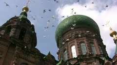 Flying pigeons in front of St. Sophia church, Harbin / China Stock Footage