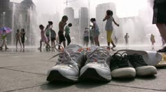 Children play with a water fountain, their shoes stand on the side, China Stock Footage