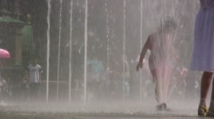 Chinese girl plays with a water fountain in Harbin, China Stock Footage