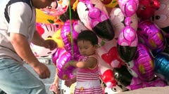 Chinese kid holding a lot of balloons, laughing and smiling Stock Footage