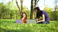 Stock Video Footage of Young happy female friends with laptop in the park, dolly shot HD