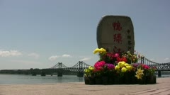 Monument in Dandong, with the bridge to North Korea in the background Stock Footage