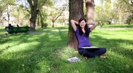 Happy female student with laptop relaxing in the park, dolly shot HD Stock Footage