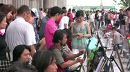 Street artists paint tourists on the streets of Harbin in China Stock Footage