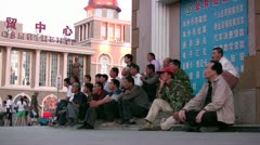 Migrant workers watching public tv in Russian Chinese town Stock Footage