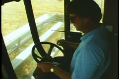 Interior cab of combine and driver harvesting wheat in Nebraska Stock Footage