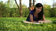 Young happy girl reading book in the park, dolly shot HD Stock Footage
