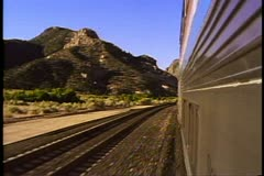 "Amtrak's ""Desert Wind"", POV, tracks, silver streamliner train, rugged vista Stock Footage"