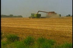 Truck alongside combine collecting wheat Stock Footage
