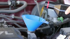 Motor oil poured into funnel Stock Footage