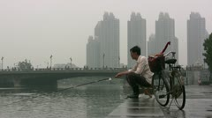 A man parks his bicycle and goes fishing in Tianjin, China - stock footage